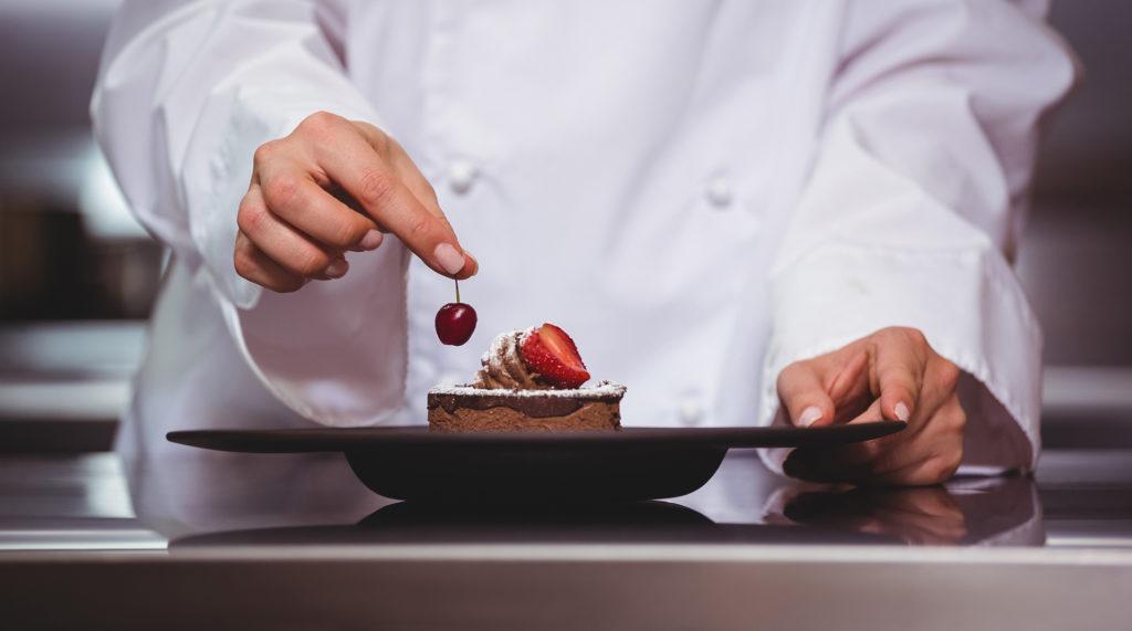 Pâtissière effectuant le dressage d'un dessert