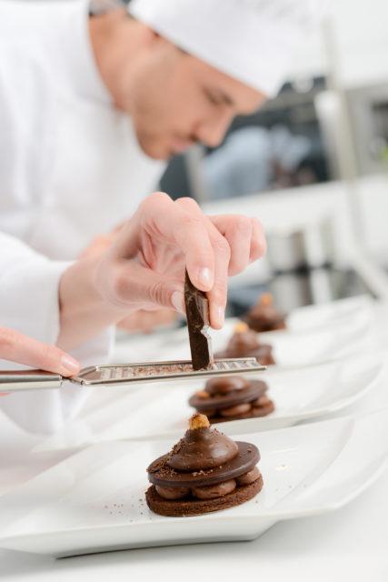 Pâtissier de restaurant en train de dresser des desserts